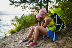 Teenager travelers with backpacks sitting on coast. Wanderlust travel concept Stock Images
