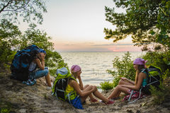 Teenager travelers with backpacks sitting on coast. Wanderlust travel concept Stock Image