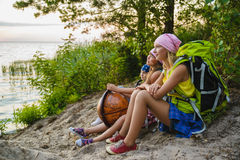 Teenager travelers with backpacks sitting on coast. Wanderlust travel concept Royalty Free Stock Image
