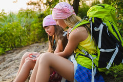 Teenager travelers with backpacks sitting on coast. Wanderlust travel concept Stock Photography