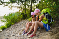 Teenager travelers with backpacks sitting on coast. Wanderlust travel concept Royalty Free Stock Photo
