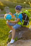 Teenager travelers with backpacks sitting on rock. Wanderlust travel concept Royalty Free Stock Photos