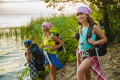 Teenager travelers with backpacks standing on coast. Wanderlust travel concept Stock Image
