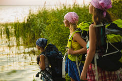 Teenager travelers with backpacks standing on coast. Wanderlust travel concept Stock Photography
