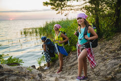 Teenager travelers with backpacks standing on coast. Wanderlust travel concept Royalty Free Stock Images