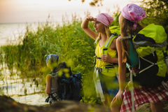 Teenager travelers with backpacks standing on coast. Wanderlust travel concept Stock Photo
