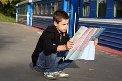 Teenager Traveling. Young traveler sitting near the train and sees a map Royalty Free Stock Image