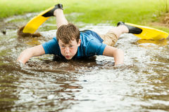 Teenager trying to swim in large puddle. Serious male teenager in diving fins trying to swim in large shallow backyard puddle Royalty Free Stock Images