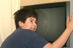 Teenager and TV set. The teenager embraces the TV set Royalty Free Stock Photography