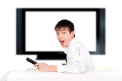 Teenager and tv-set. Amazed teenager sitting on the sofa and watching tv-set Stock Photography