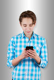 Teenager is typing  message in phone. Stock Images