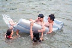 Teenager und Mädchen, die im Fluss im Sommer schwimmen und spielen stockfotos