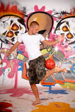 Teenager urban graffiti. Handsome teenager in front of graffiti wall playing with soccer ball, urban setting.  Studio shoot Royalty Free Stock Photography
