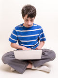 Teenager using computer. A young male teenager sitting down indian style using a laptop computer Stock Images