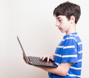 Teenager using computer, checking on his social Royalty Free Stock Images