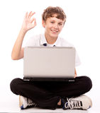 Teenager using laptop - ok gesture. Attractive teen Boy with Laptop Computer giving ok gesture on white background royalty free stock images