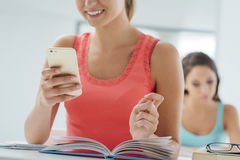 Teenager using mobile in the classroom Stock Photography