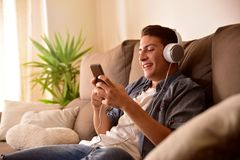 Teenager using a mobile phone with headphones sitting. On a sofa at home Stock Photo
