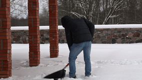 Teenager using snow shovel in winter stock footage