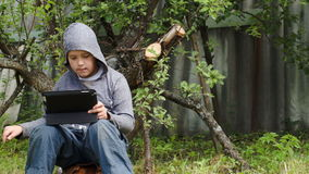 Teenager using tablet computer in the yard. Dolly shot of a teenager in the yard using touchpad on summer day. He doing it in a jerk stock footage