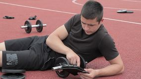 Teenager using tablet PC near dumbbells stock video