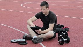 Teenager using tablet PC at outdoor on sports ground. In summer day stock video