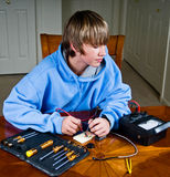 Teenager using a voltmeter. Teenage boy measures voltage across a circuit in a science project royalty free stock photo