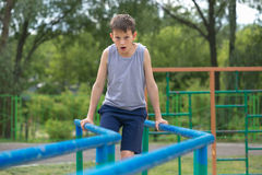 The teenager in a vest is engaged on uneven bars Royalty Free Stock Image
