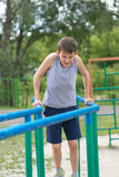 The teenager in a vest is engaged on uneven bars Royalty Free Stock Photos