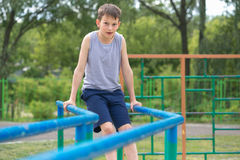 The teenager in a vest is engaged on uneven bars.  royalty free stock images