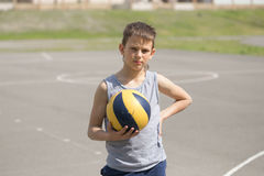 A teenager in a vest holds a ball in his hand.  Royalty Free Stock Photography