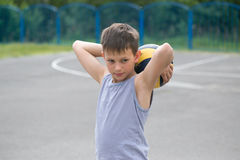 A teenager in a vest holds a ball in his hand.  Stock Photography