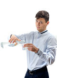 Teenager waiter pouring water from glass bottle into a glass iso Stock Images