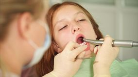 Teenager is waiting for the completion of dental treatment of teeth in hospital stock video footage