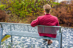 Teenager waiting for his love girlfriend on date. Young teen boy on date waiting for his girlfriend on valentine outdoor on park bench, sitting sad and alone royalty free stock photography