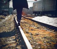 A  teenager is walking along the railway tracks stock images
