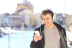 Teenager walking listening music from smart phone. Front view of a teenager walking towards camera listening music with headphones from smart phone in a Royalty Free Stock Photos
