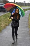 Teenager walking in the rain. Teenage girl with colorful umbrella walking in the rain Stock Photography