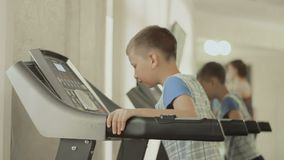 The teenager walks on the treadmill. Teenager walks on the treadmill. the kid is exercising in the gym near the mirror. Boy cares about his body, figure stock footage