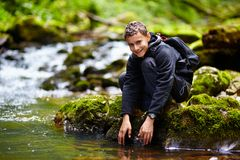 Teenager washing his hands in a river Stock Photography
