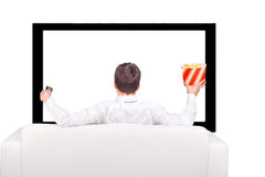 Teenager watch the Tv. Teenager with Remote Control and Popcorn sitting on the Sofa and watching Tv-set Royalty Free Stock Photo