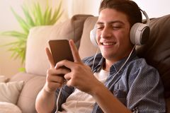 Teenager watching multimedia content with headphones sitting on Stock Images