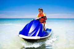 Teenager on water scooter. Teen age boy water skiing. Teen age boy skiing on water scooter. Young man on personal watercraft in tropical sea. Active summer Royalty Free Stock Photo