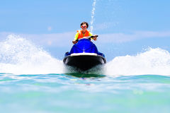 Teenager on water scooter. Teen age boy water skiing. Teenager on water scooter. Teen age boy skiing. Young man on personal watercraft in tropical sea. Active Stock Photo