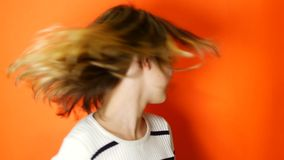 Teenager waving her hair on a coral background stock footage
