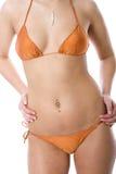 Teenager wearing bikini. Close up of slim teenager wearing orange bikini, isolated on white background Royalty Free Stock Photography