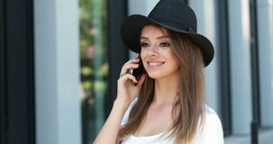 Teenager wearing hat walking and talking using her smartphone stock footage