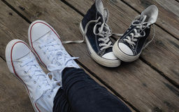 Teenager wearing white shoes sitting next to black snickers, choice concept. Teenager wearing white shoes sitting next to black snickers on the wooden bridge Stock Photos