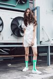 Teenager in white dress and green socks on the street. Streetstyle, fashion. Teenager in white dress and green socks on the street. Propellers on background Royalty Free Stock Photos