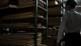 A teenager in a white shirt walks between bookshelves with old documents in libraries searching for literature. Basement archive r. A teenager in a white shirt stock video